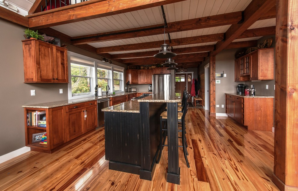 Inspiration for a large rustic l-shaped light wood floor eat-in kitchen remodel in Portland Maine with an undermount sink, flat-panel cabinets, medium tone wood cabinets, stainless steel appliances, granite countertops and an island