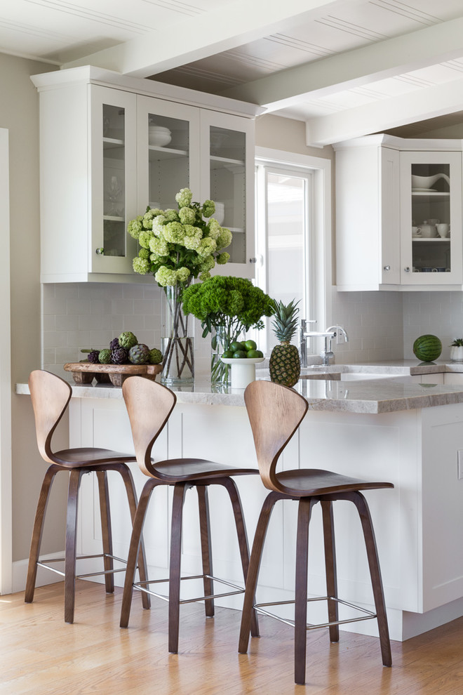Example of a mid-sized transitional u-shaped light wood floor and brown floor eat-in kitchen design in San Francisco with glass-front cabinets, white cabinets, subway tile backsplash, a peninsula, granite countertops, white backsplash, a farmhouse sink and stainless steel appliances