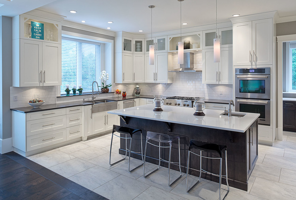 Example of a large transitional l-shaped ceramic floor eat-in kitchen design in Vancouver with a double-bowl sink, shaker cabinets, white cabinets, solid surface countertops, white backsplash, ceramic backsplash, stainless steel appliances and an island
