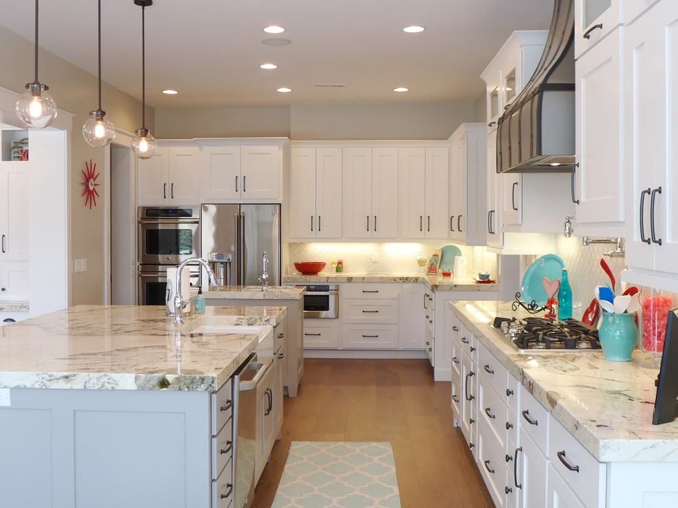 Example of a classic medium tone wood floor and brown floor open concept kitchen design in Salt Lake City with a farmhouse sink, white cabinets, granite countertops, white backsplash, stainless steel appliances, two islands, shaker cabinets and subway tile backsplash