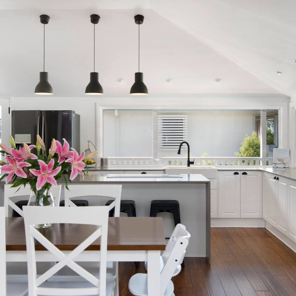 Inspiration for a large modern l-shaped bamboo floor and brown floor open concept kitchen remodel in Brisbane with a farmhouse sink, shaker cabinets, white cabinets, quartz countertops, stainless steel appliances, an island and gray countertops