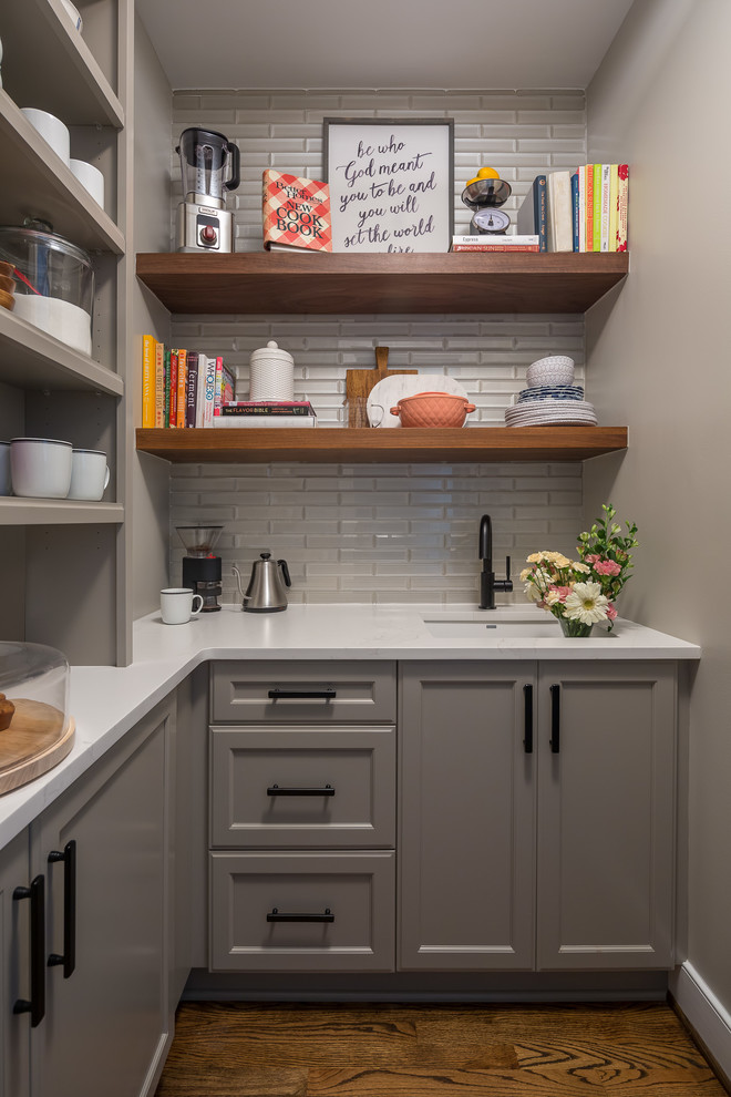 Example of a transitional l-shaped brown floor and medium tone wood floor kitchen pantry design in Raleigh with an undermount sink, recessed-panel cabinets, gray cabinets, gray backsplash, glass tile backsplash and white countertops
