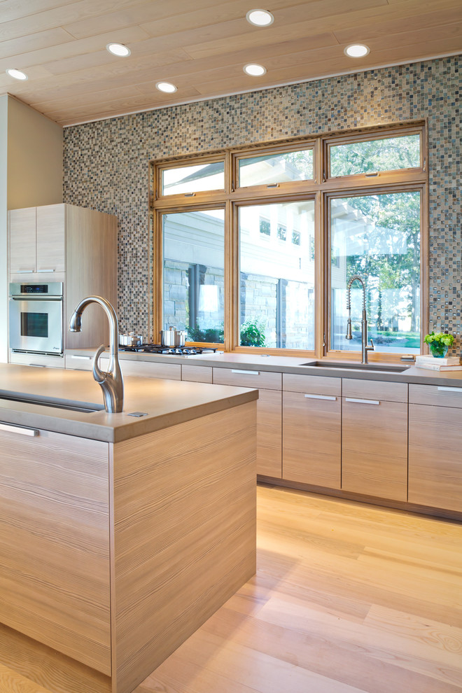 Example of a trendy light wood floor kitchen design in Minneapolis with multicolored backsplash, mosaic tile backsplash, an undermount sink, flat-panel cabinets and light wood cabinets