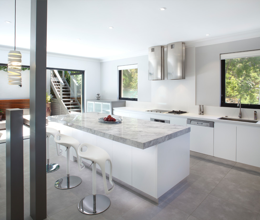 Eat-in kitchen - mid-sized contemporary single-wall eat-in kitchen idea in Sydney with an undermount sink, flat-panel cabinets, white cabinets, granite countertops, white backsplash, glass sheet backsplash, stainless steel appliances and an island