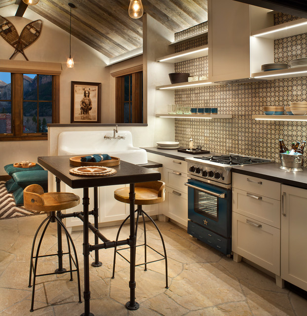 Kitchen - rustic l-shaped kitchen idea in Denver with a farmhouse sink, shaker cabinets, white cabinets, multicolored backsplash, colored appliances and an island