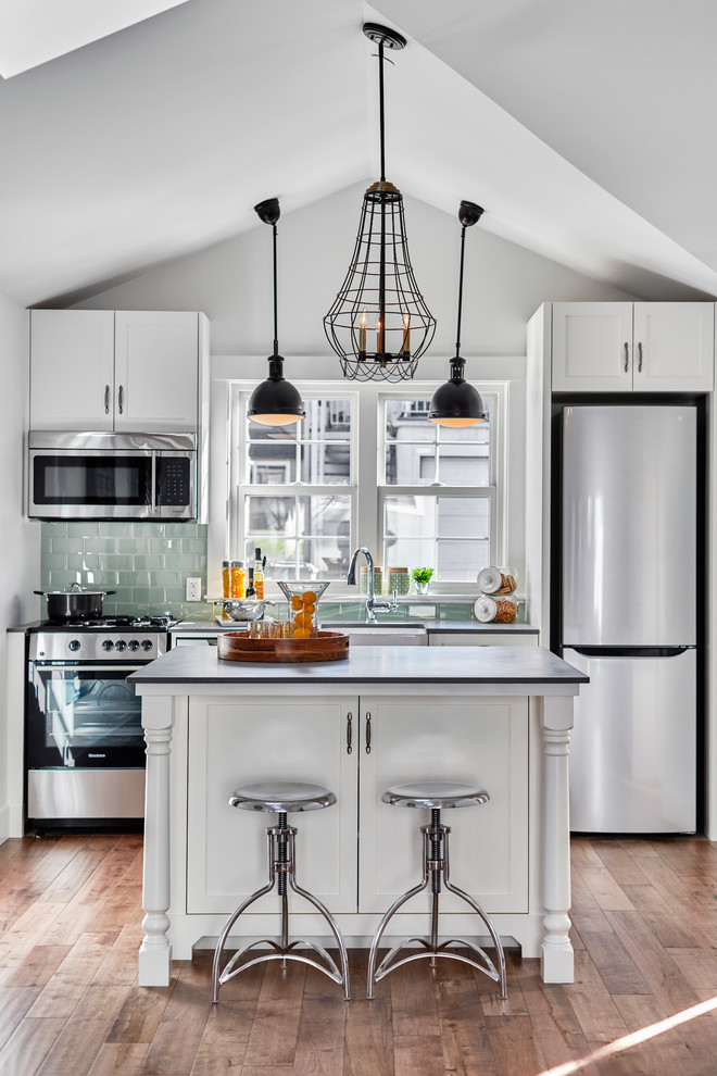 Small transitional kitchen photo in Vancouver with green backsplash and an island