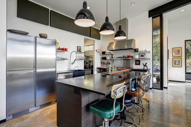 Urban l-shaped concrete floor and gray floor kitchen photo in Seattle with a farmhouse sink, flat-panel cabinets, dark wood cabinets, stainless steel appliances and an island