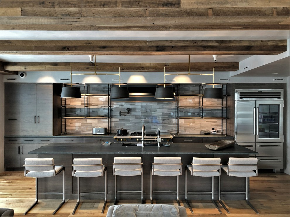 Eat-in kitchen - large contemporary u-shaped medium tone wood floor and brown floor eat-in kitchen idea in Denver with a farmhouse sink, flat-panel cabinets, light wood cabinets, stainless steel appliances, an island, black countertops, soapstone countertops, gray backsplash and marble backsplash