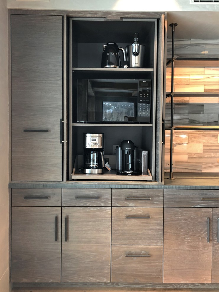 Example of a large trendy u-shaped medium tone wood floor and brown floor eat-in kitchen design in Denver with a farmhouse sink, flat-panel cabinets, light wood cabinets, stainless steel appliances, an island, concrete countertops, gray backsplash, marble backsplash and gray countertops
