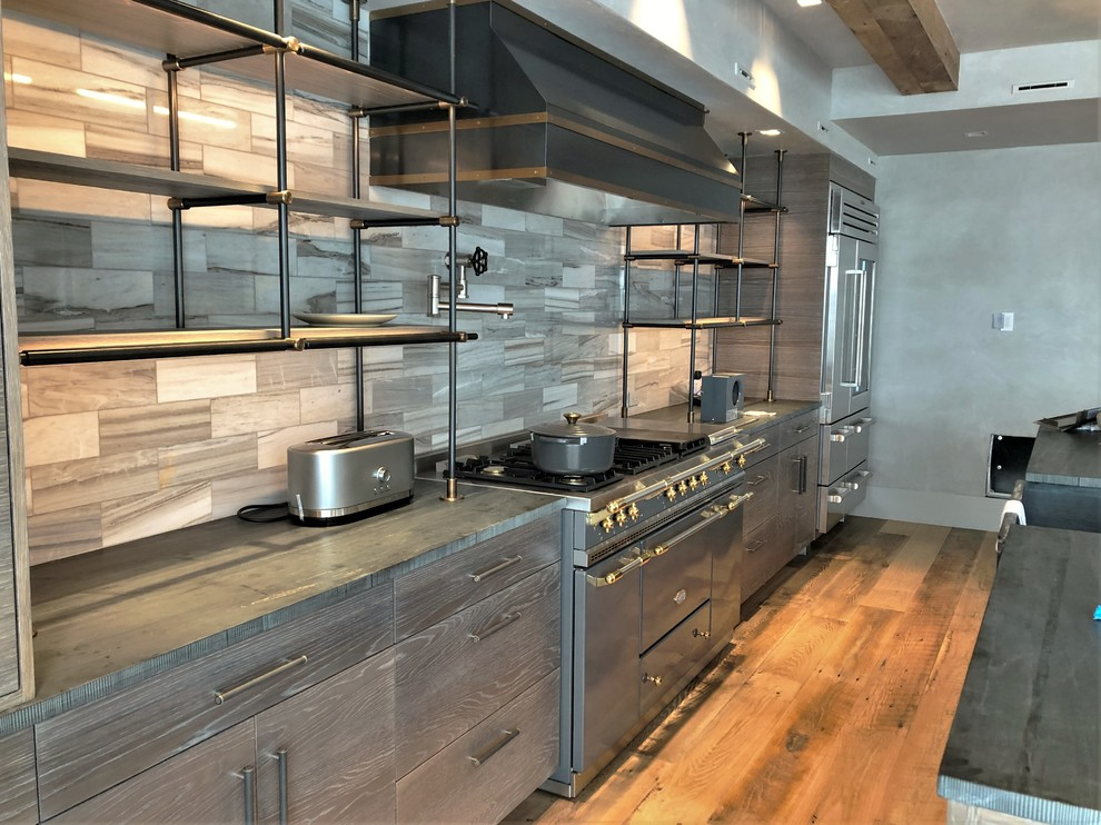 Example of a large trendy u-shaped medium tone wood floor and brown floor eat-in kitchen design in Denver with a farmhouse sink, flat-panel cabinets, light wood cabinets, quartzite countertops, beige backsplash, porcelain backsplash, stainless steel appliances, an island and black countertops