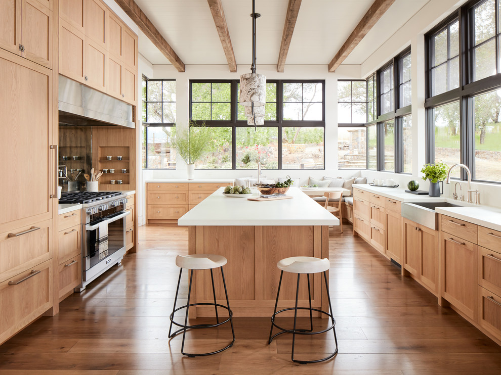 Example of a cottage u-shaped medium tone wood floor and brown floor eat-in kitchen design in San Francisco with a farmhouse sink, shaker cabinets, medium tone wood cabinets, stainless steel appliances, an island and white countertops