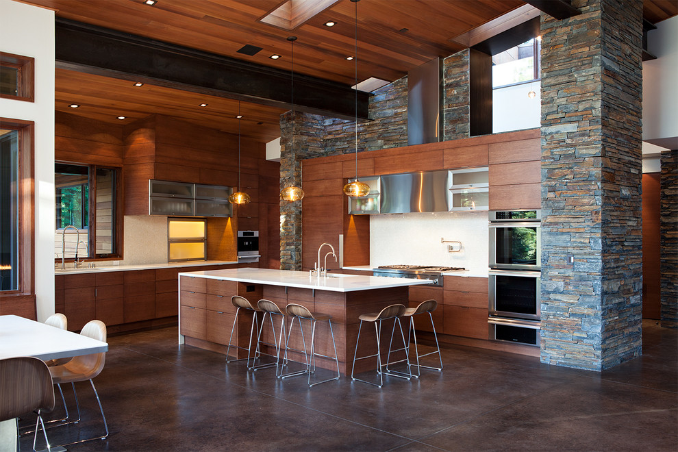 Example of a trendy brown floor open concept kitchen design in Sacramento with flat-panel cabinets, dark wood cabinets and stainless steel appliances