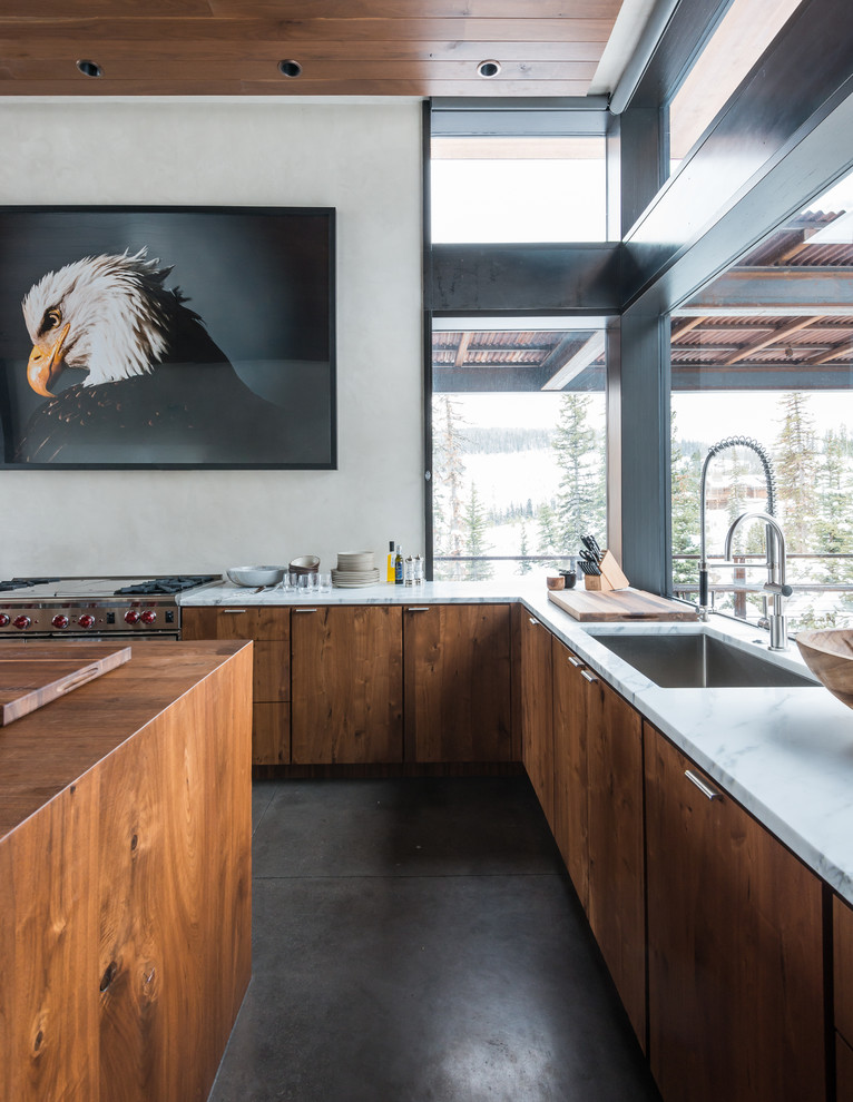Example of a large mountain style l-shaped concrete floor eat-in kitchen design in Other with an undermount sink, flat-panel cabinets, an island, medium tone wood cabinets, marble countertops and stainless steel appliances