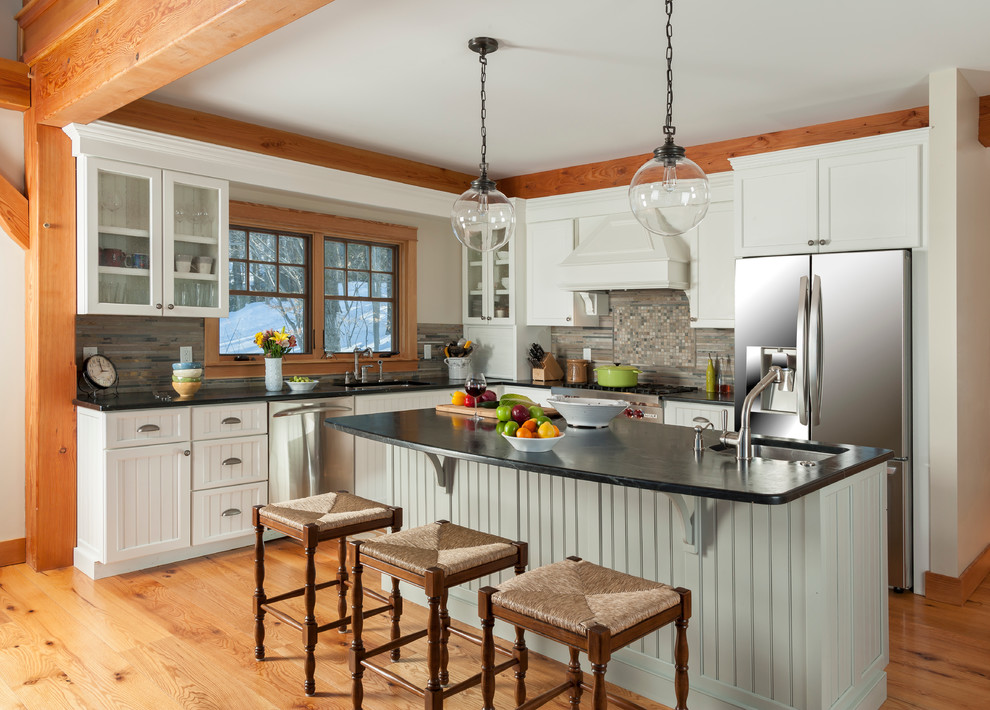 Eat-in kitchen - mid-sized rustic l-shaped medium tone wood floor eat-in kitchen idea in Burlington with white cabinets, granite countertops, multicolored backsplash, an island, an undermount sink, recessed-panel cabinets, stone tile backsplash and stainless steel appliances