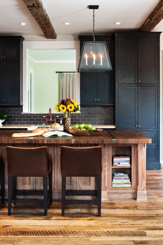 Large mountain style medium tone wood floor kitchen photo in Richmond with shaker cabinets, black cabinets, wood countertops, gray backsplash, stainless steel appliances and an island