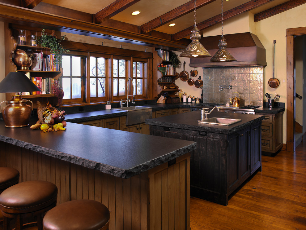 Inspiration for a large rustic u-shaped dark wood floor enclosed kitchen remodel in Boise with a farmhouse sink, stainless steel appliances, an island, shaker cabinets, soapstone countertops, gray backsplash and dark wood cabinets
