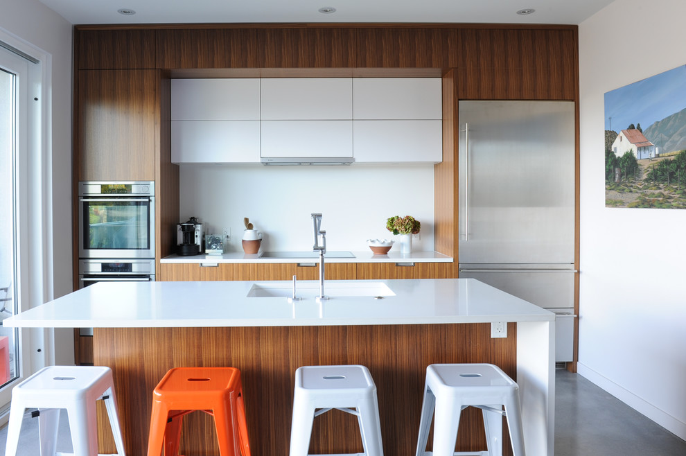 Inspiration for a small contemporary galley concrete floor and gray floor kitchen remodel in Vancouver with flat-panel cabinets, medium tone wood cabinets, white backsplash, stainless steel appliances, an island and a single-bowl sink