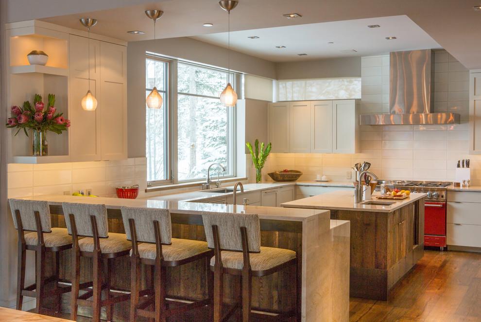 Kitchen - large modern u-shaped medium tone wood floor kitchen idea in Denver with an undermount sink, recessed-panel cabinets, white cabinets, quartzite countertops, white backsplash, ceramic backsplash, stainless steel appliances and an island