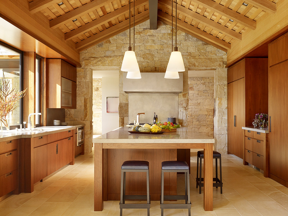 Kitchen - country galley limestone floor and beige floor kitchen idea in San Francisco with an undermount sink, flat-panel cabinets, medium tone wood cabinets, limestone countertops, paneled appliances, an island and limestone backsplash