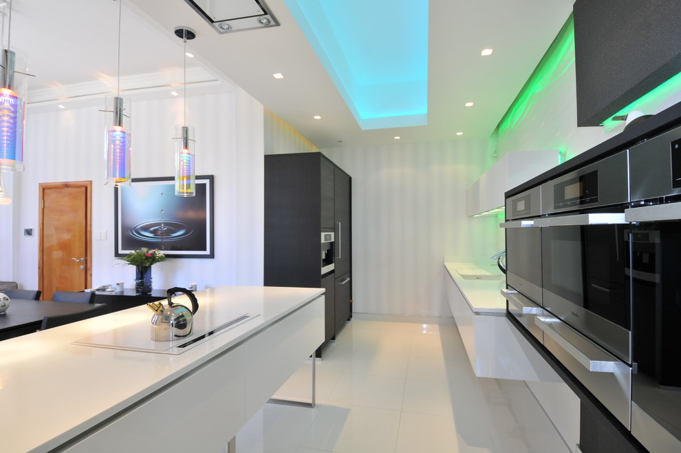 Inspiration for a contemporary kitchen remodel in Manchester with flat-panel cabinets, black cabinets, stainless steel appliances and an island