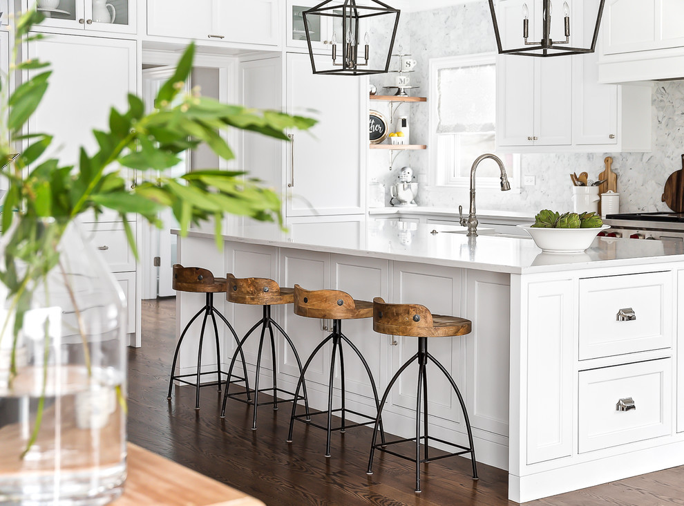 Inspiration for a large transitional eat-in kitchen in Chicago with a farmhouse sink, beaded inset cabinets, white cabinets, quartz benchtops, grey splashback, marble splashback, stainless steel appliances, medium hardwood floors, an island and brown floor.
