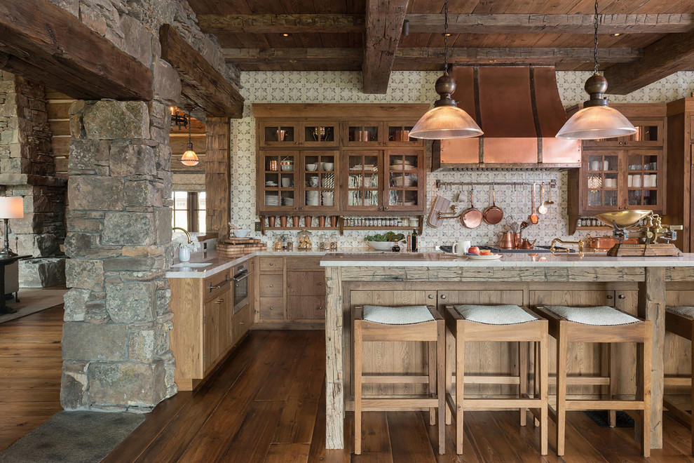 Mountain style l-shaped medium tone wood floor kitchen photo in Other with glass-front cabinets, medium tone wood cabinets, multicolored backsplash and an island