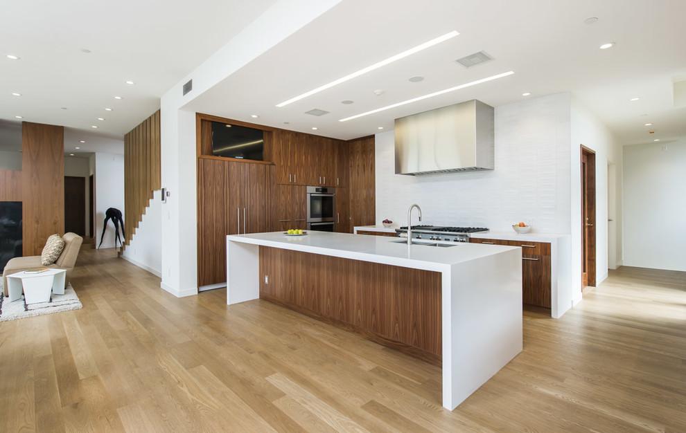 Modelo de cocinas en U contemporáneo con fregadero bajoencimera, armarios con paneles lisos, puertas de armario de madera en tonos medios, salpicadero blanco, electrodomésticos de acero inoxidable, suelo de madera clara, una isla y de obra