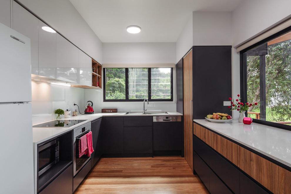 Réalisation d'une petit cuisine design en U avec des portes de placard en bois sombre, une crédence blanche, un électroménager en acier inoxydable, un sol en bois brun, aucun îlot et un placard à porte plane.