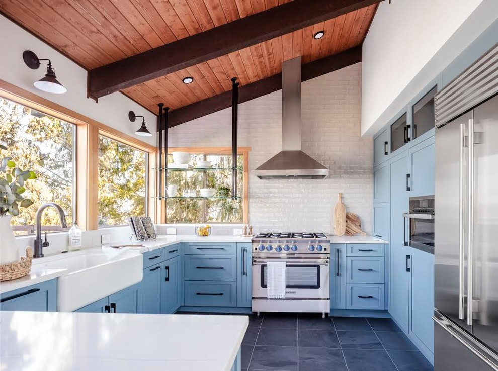 Example of a large minimalist u-shaped slate floor and black floor kitchen design in Seattle with a farmhouse sink, shaker cabinets, blue cabinets, quartzite countertops, white backsplash, subway tile backsplash, stainless steel appliances, a peninsula and white countertops
