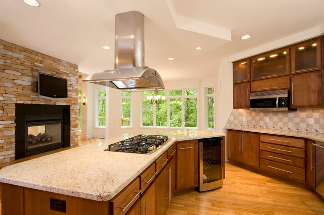 Eat-in kitchen - large transitional galley light wood floor eat-in kitchen idea in Other with flat-panel cabinets, medium tone wood cabinets, granite countertops, beige backsplash, ceramic backsplash, stainless steel appliances and an island