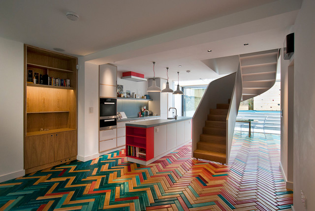 Example of an eclectic galley multicolored floor and painted wood floor open concept kitchen design in London with flat-panel cabinets, white cabinets, concrete countertops, gray backsplash, black appliances and an island