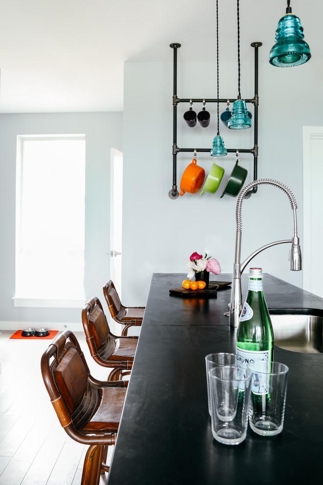 Idée de décoration pour une cuisine ouverte design avec un évier encastré, un plan de travail en stéatite, un îlot central, un sol gris et un plan de travail noir.