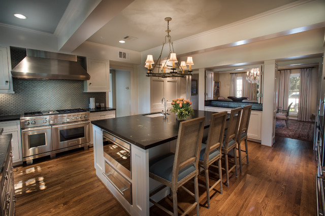 Large elegant galley medium tone wood floor enclosed kitchen photo in Houston with a farmhouse sink, shaker cabinets, white cabinets, granite countertops, blue backsplash, subway tile backsplash, stainless steel appliances and an island