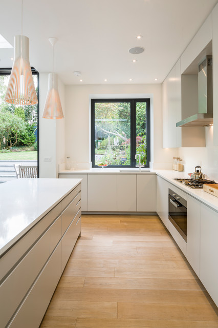Medium sized contemporary l-shaped kitchen in London with an island, flat-panel cabinets, engineered stone countertops, stainless steel appliances, a submerged sink, light hardwood flooring and white splashback.