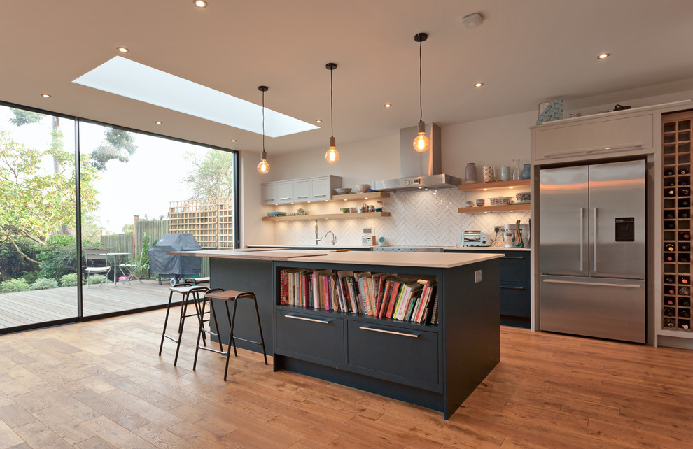 Mid-sized trendy single-wall medium tone wood floor and brown floor open concept kitchen photo in Essex with an undermount sink, flat-panel cabinets, blue cabinets, white backsplash, porcelain backsplash, stainless steel appliances and an island