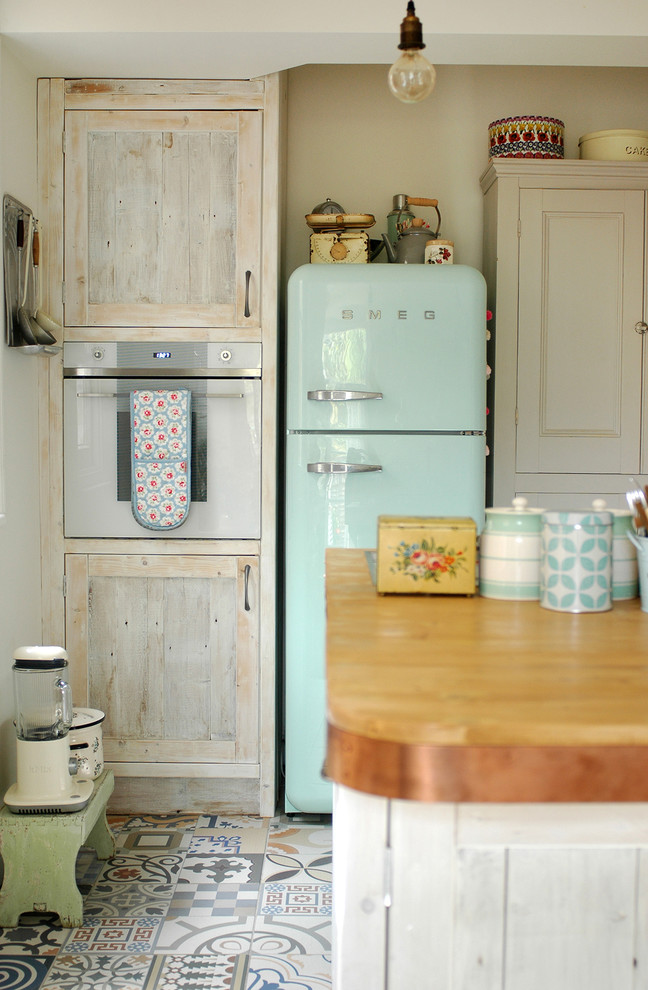 Example of a danish kitchen design in Other with shaker cabinets, light wood cabinets, colored appliances and an island