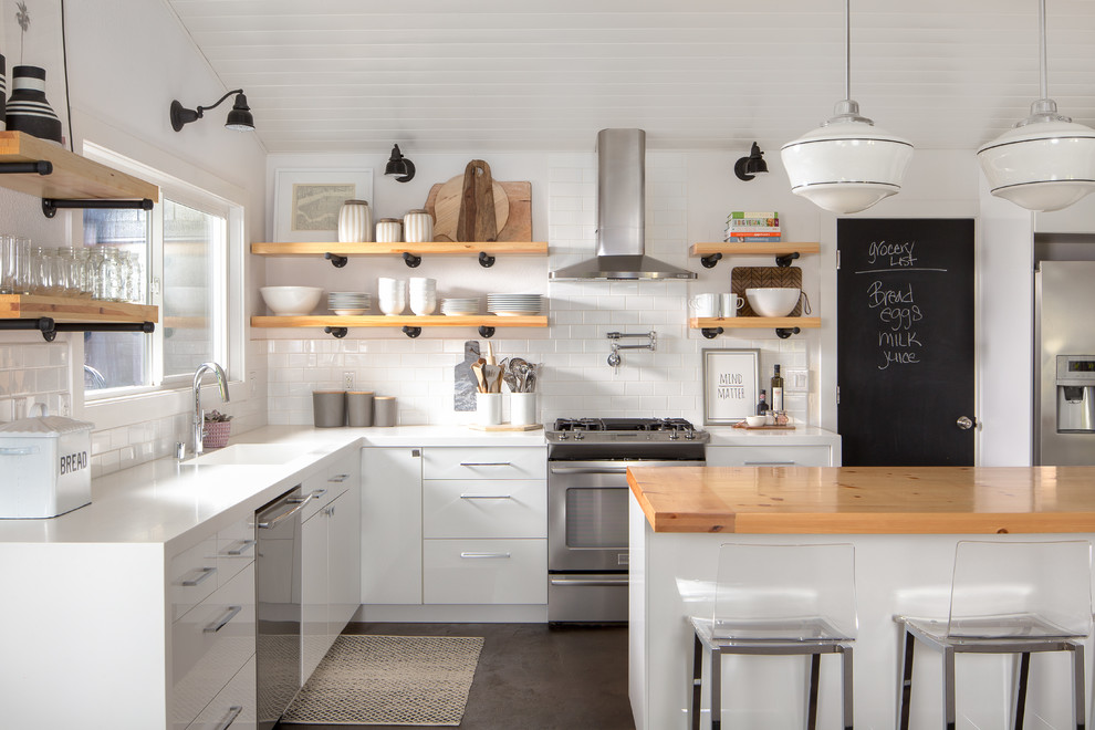 Example of a cottage l-shaped kitchen design in Sacramento with an integrated sink, flat-panel cabinets, white cabinets, wood countertops, white backsplash, subway tile backsplash, stainless steel appliances and an island