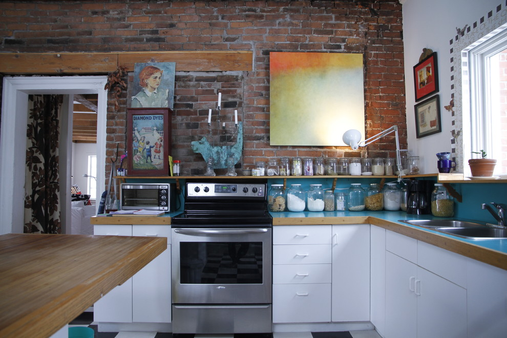 Eclectic kitchen photo in Montreal with laminate countertops, a drop-in sink, flat-panel cabinets, white cabinets, stainless steel appliances and turquoise countertops