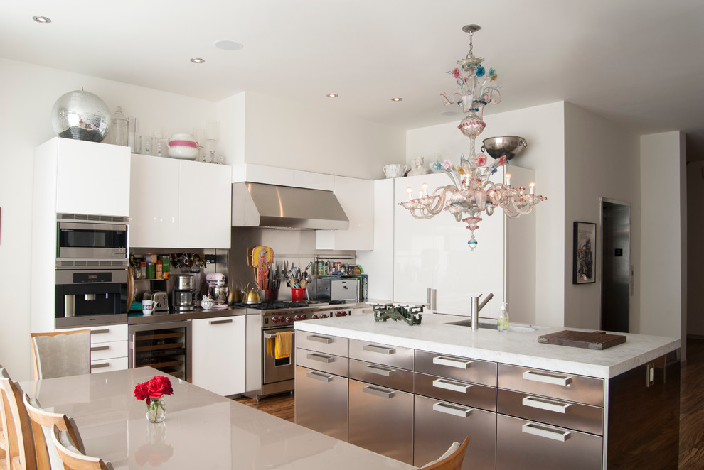 Large trendy medium tone wood floor eat-in kitchen photo in New York with an undermount sink, flat-panel cabinets, white cabinets, metallic backsplash, stainless steel appliances and an island