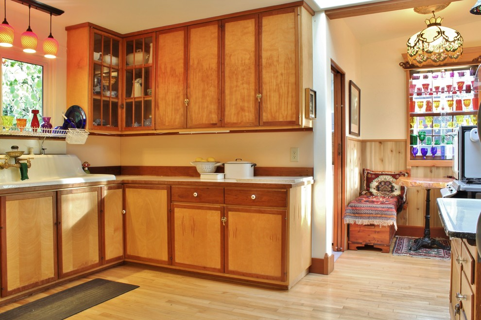 Example of an eclectic eat-in kitchen design in Seattle with a drop-in sink, flat-panel cabinets and medium tone wood cabinets