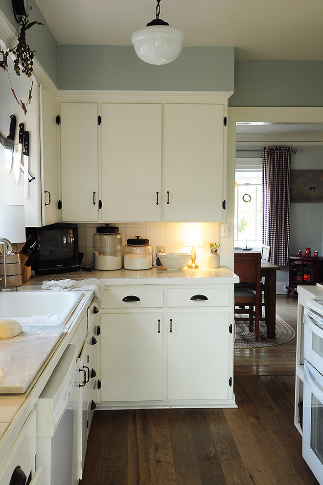 Example of a classic kitchen design in Portland with a drop-in sink, tile countertops and white appliances