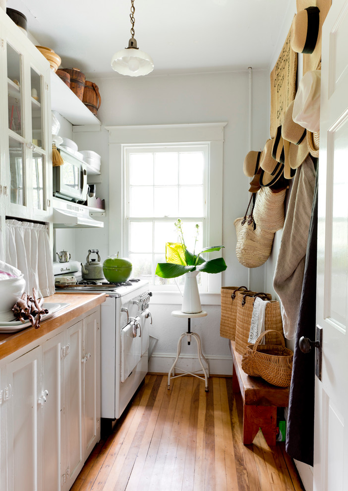 Inspiration for a timeless medium tone wood floor kitchen remodel in New York with wood countertops and white appliances