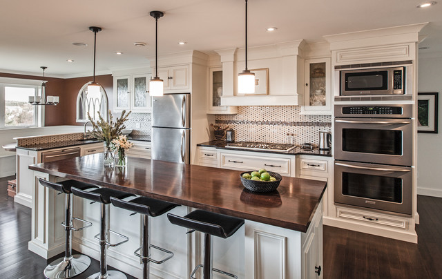 Transitional l-shaped kitchen photo in Other with recessed-panel cabinets, white cabinets, wood countertops, multicolored backsplash, mosaic tile backsplash and stainless steel appliances