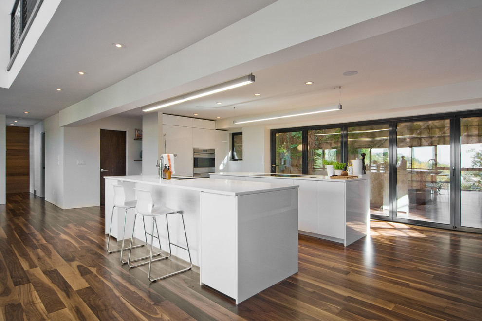 Inspiration for a modern brown floor open concept kitchen remodel in Salt Lake City with white cabinets, flat-panel cabinets and paneled appliances