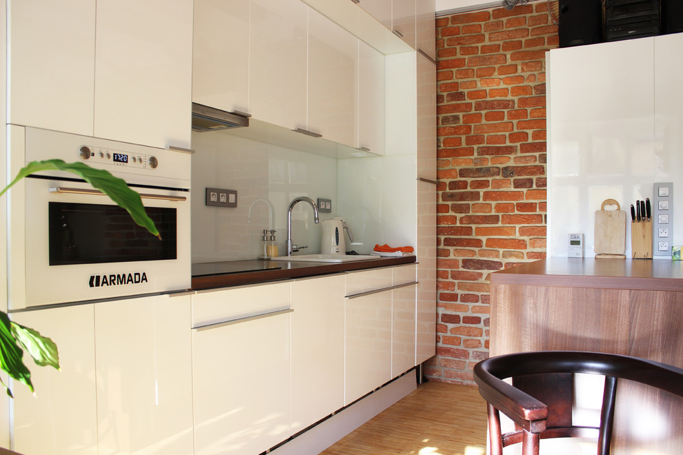 Inspiration for an industrial galley kitchen remodel in Other with flat-panel cabinets, a drop-in sink, white cabinets, white backsplash, white appliances and glass sheet backsplash