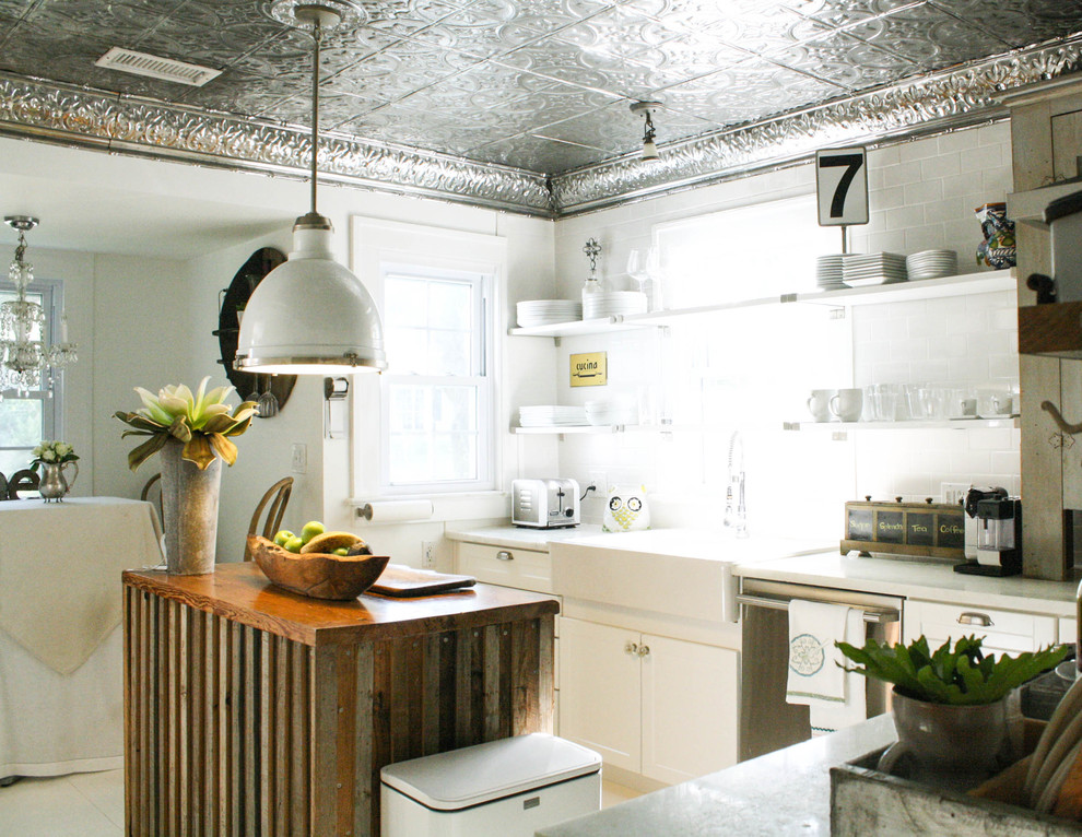 Eat-in kitchen - eclectic l-shaped eat-in kitchen idea in Tampa with a farmhouse sink, white backsplash, subway tile backsplash, stainless steel appliances and white cabinets