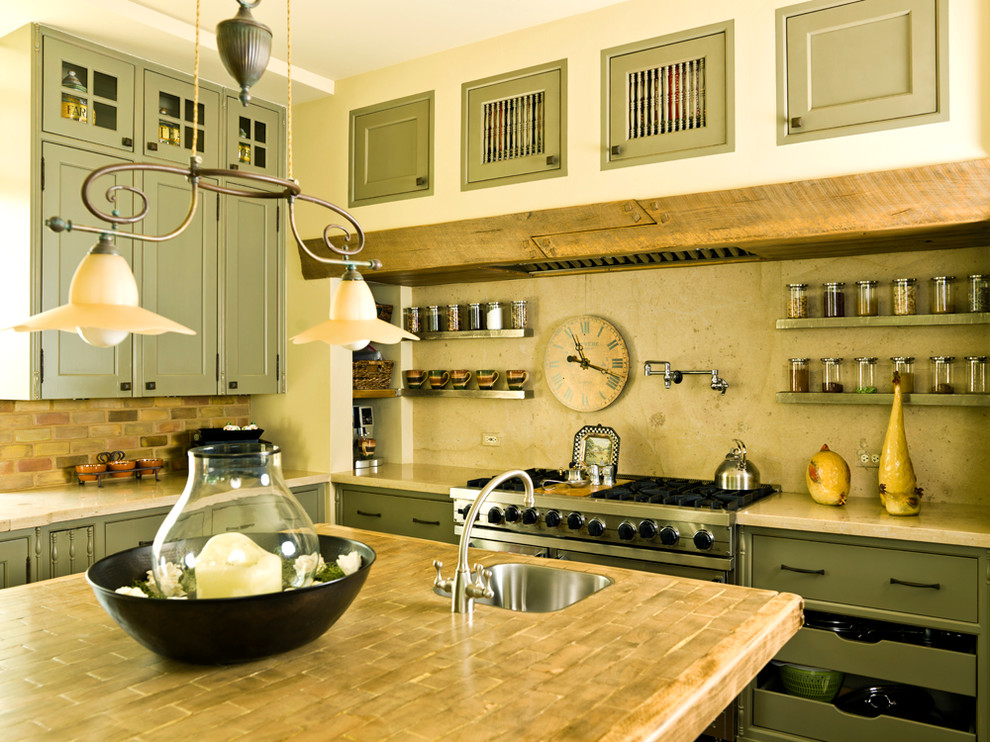 Example of a classic kitchen design in Chicago with wood countertops, recessed-panel cabinets, green cabinets, stainless steel appliances, beige backsplash and limestone backsplash
