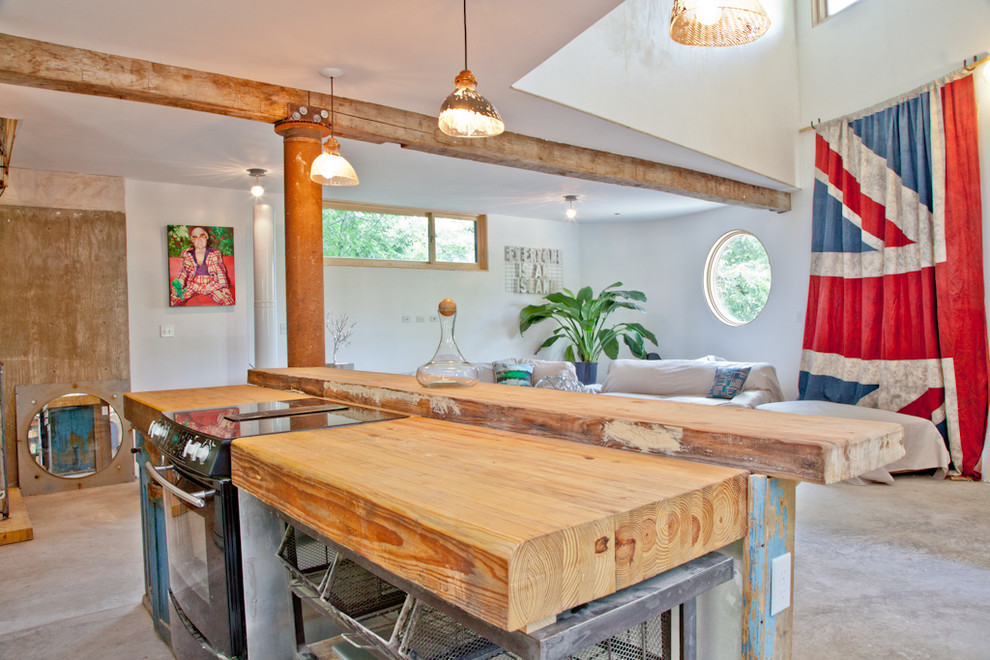 Inspiration for an eclectic kitchen remodel in Austin with wood countertops and black appliances