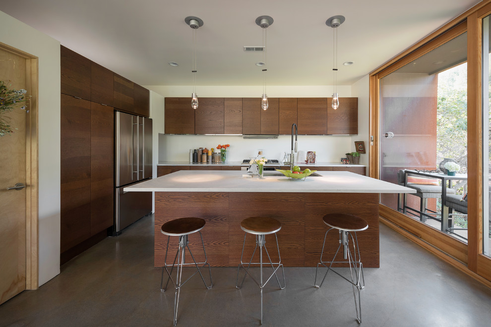 Inspiration for a contemporary galley concrete floor kitchen remodel in Salt Lake City with an undermount sink, flat-panel cabinets, dark wood cabinets, stainless steel appliances and an island