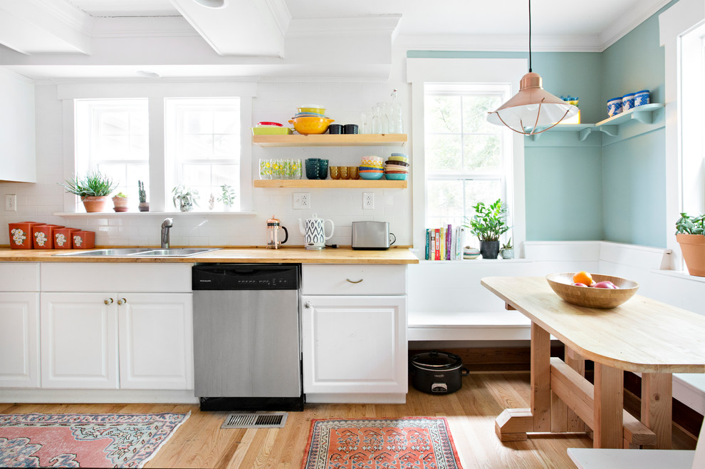 Example of a country single-wall light wood floor and beige floor eat-in kitchen design in Nashville with a double-bowl sink, raised-panel cabinets, white cabinets, wood countertops, white backsplash, subway tile backsplash, stainless steel appliances and no island